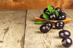 Prunes fraîches sur une table en bois Ventes de récolte de fruit de fruit frais Photo libre de droits