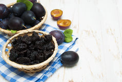 Prunes. With fresh plums on a wooden background Stock Photos