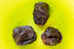 Prunes on a green plate close up Stock Image