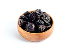 Prunes inside wooden bowl. On white isolated color background royalty free stock photos