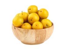 Prunes jaunes fraîches dans la cuvette en bois au-dessus du blanc Photographie stock