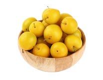Prunes jaunes fraîches dans la cuvette en bois au-dessus du blanc Photos libres de droits