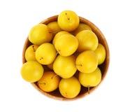 Prunes jaunes fraîches dans la cuvette en bois au-dessus du blanc Images stock