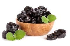 Prunes ou pruneaux avec une feuille en bon état dans la cuvette en bois sur le fond blanc Photographie stock libre de droits