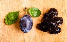 Prunes sèches et fruit frais de pruneau sur la table en bois photo libre de droits