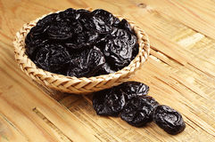 Prunes in a wicker bowl and near Stock Photography