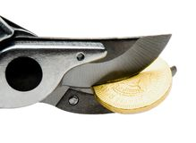 Pruning shears cutting coin Royalty Free Stock Photography