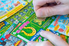 Man hand scratching a Polish Lotto lottery scratch card with coin. royalty free stock photo