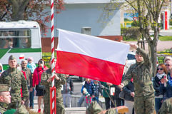 PRUSZCZ GDANSKI, POLAND - May 3, 2017: Polish soldier hanging polish flag during celebrations of May 3rd Constitution. Man hanging polish flag during Royalty Free Stock Photo