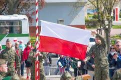 PRUSZCZ GDANSKI, POLEN - 3. Mai 2017: Polnischer Soldat, der polnische Flagge während der Feiern der vom 3. Mai Konstitution häng Lizenzfreies Stockfoto