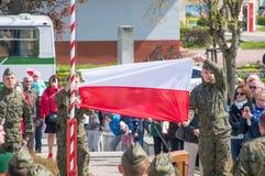 PRUSZCZ GDANSKI, POLEN - Maj 3, 2017: Polsk soldat som hänger den polska flaggan under berömmar av den Maj 3rd konstitutionen på  Arkivbilder