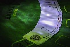Pryda av spela kort på den gröna tabellen för blackjacken som tänds med partiljus arkivbilder