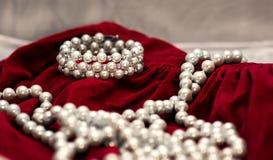 Pryda med pärlor armbandet och halsbandet på röd sammet, royaltyfri foto