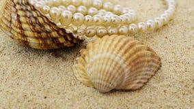 Pryder med pärlor halsbandet på sand