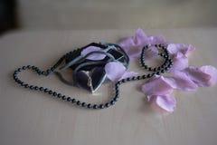 Pryder med pärlor rosblad med hjärta på tabel Arkivfoto