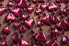 Pryder med pärlor röda valentin för bakgrund girlanden på gammal träbrädehor Fotografering för Bildbyråer