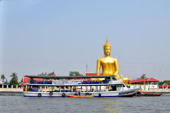 Prydnad: enorm guldbuddha staty nära floden Arkivbild