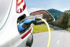 Prymka władza kabla elektryczna dostawa podczas ładować przy ev samochodowym elektrycznym pojazdem ładuje na nieba i drogi tle zdjęcia royalty free