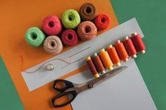 Przędze nici dla dziać w różnych kolorach na zieleni i kolorze żółtym fotografia stock