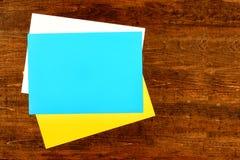 Prześcieradło biały, żółty i błękitny biuro papieru kłamstwo na drewnianym tle, majcher na drewnianym stole, kopii przestrzeń zdjęcia stock