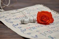 Prześcieradło muzyka z słuchawkami i pomarańcze różą zdjęcie royalty free
