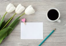 Prze?cierad?o papier z czerwonym pi?rem, kwiatami i fili?anka kawy, k?ama na bia?ym drewnianym stole Opuszcza notatk? na stole zdjęcia royalty free