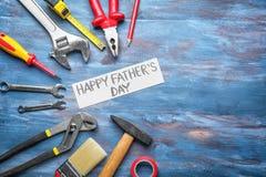 Prześcieradło papier z teksta ojca Szczęśliwym dniem i setem narzędzia na drewnianym tle obraz stock