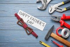 """Prześcieradło papier z tekstem, Szczęśliwym ojcem, «s dniem"""" """"łęku krawat i set narzędzia na drewnianym tle, zdjęcie royalty free"""