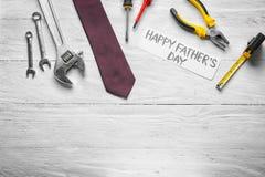 """Prześcieradło papier z tekstem, Szczęśliwym ojcem, «s dniem"""", krawatem i setem narzędzia na drewnianym tle """"«, zdjęcia stock"""