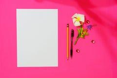 Prześcieradło pusty papier A4 z piórem, ołówek i frangipani, kwitniemy na czerwonym tle dla niektóre wiadomości lub pomysłu Zdjęcia Stock