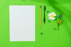 Prześcieradło pusty papier A4 z piórem, ołówek i frangipani, kwitniemy na zielonym tle dla niektóre wiadomości lub pomysłu Zdjęcie Royalty Free