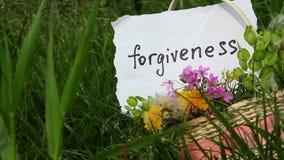 Przebaczenie, słowo na białym papierze na zielonym natury tle zbiory wideo