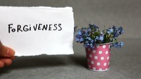 Przebaczenie - słowo na szarym tle z błękitnymi kwiatami zdjęcie wideo