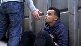 Przechodzący mężczyzna ofiary pomocną dłonią uliczny dziecko, dobroć i dobroczynność, zdjęcie stock