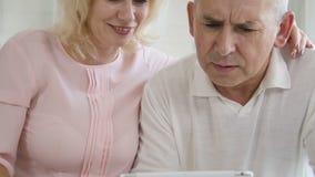 Przechodzić na emeryturę żony nauczania mąż używać pastylka komputer w nowożytnej mieszkanie kuchni zbiory wideo
