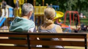 Przechodzić na emeryturę kobieta na ławce w parkowych dopatrywanie wnukach i mężczyzna, szczęśliwi wspominki zdjęcia stock