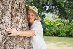 Przechodzić na emeryturę kobieta ściska drzewa ono uśmiecha się przy kamerą zdjęcia royalty free