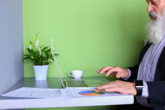 Przechodzić na emeryturę stary polityczny mężczyzna pracuje przy komputerem w biurze w dniu Fotografia Stock