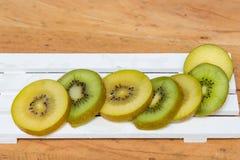 przecięcie kiwi Żółta kiwi i zieleń kiwi owoc na drewnianym Fotografia Stock