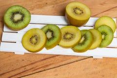 przecięcie kiwi Żółta kiwi i zieleń kiwi owoc odizolowywająca na drewnianym Fotografia Stock