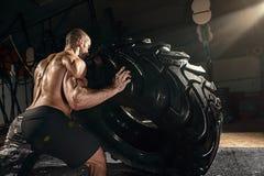Przecinający siłacza szkolenie - mężczyzna podrzuca oponę Zdjęcia Stock
