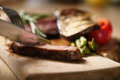 Przecinanie ziobro oka średni stek z piec na grillu warzywami Obraz Stock