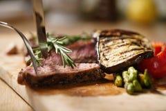 Przecinanie ziobro oka średni stek z piec na grillu warzywami Obraz Royalty Free