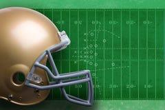 Przeciw śródpolnemu diagramowi złocisty futbolowy hełm zdjęcie stock