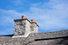 przeciw błękitny kominom dachowy niebo pokrywać strzechą Zdjęcia Stock