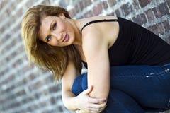 przeciw ceglanej brunetki modela ścianie Zdjęcia Stock