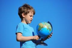 przeciw chłopiec kuli ziemskiej niebu Fotografia Stock