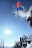 Przeciw niebieskiemu niebu narciarki doskakiwanie Zdjęcia Royalty Free