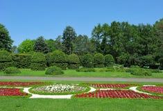Przeciw niebieskiemu niebu, pięknemu przygotowywającemu parkowi z obliczającymi krzakami, dekoracyjnym kwiatów łóżkom i wysokim z zdjęcie stock