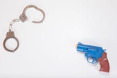 Przeciwstawiać zabawkarskiego pistolecika i kajdanki z kopii przestrzenią zdjęcia stock
